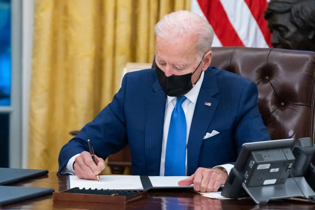 President Joe Biden signs and executive order in the Oval Office