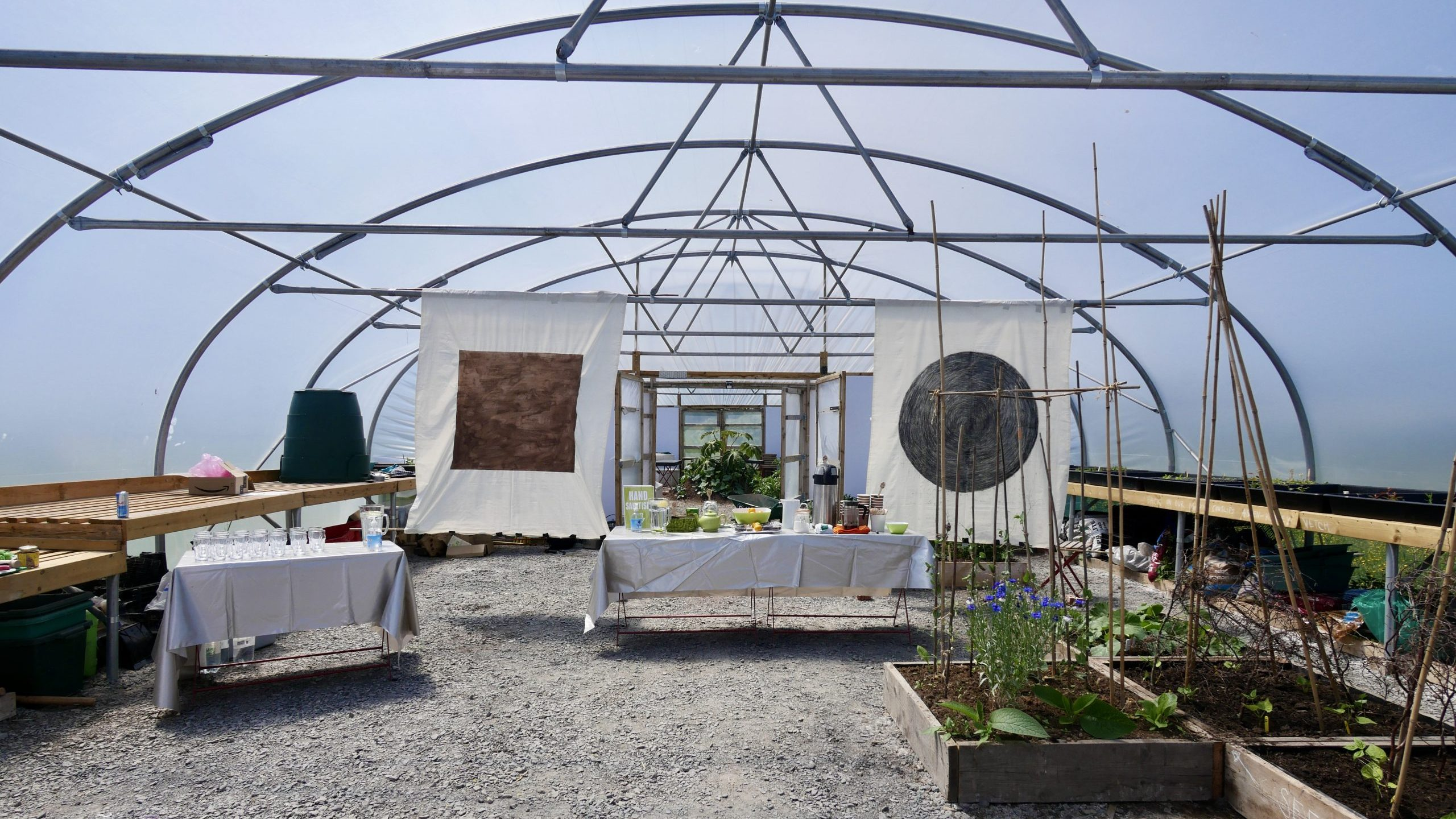 Image: Event inside poly tunnels at Allotment Soup. 2 charcoal drawings on fabric hand either side of a refreshments table.