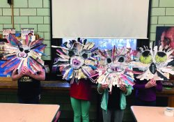 A photo of four young students. They are holding up lion masks that they made out of paper.