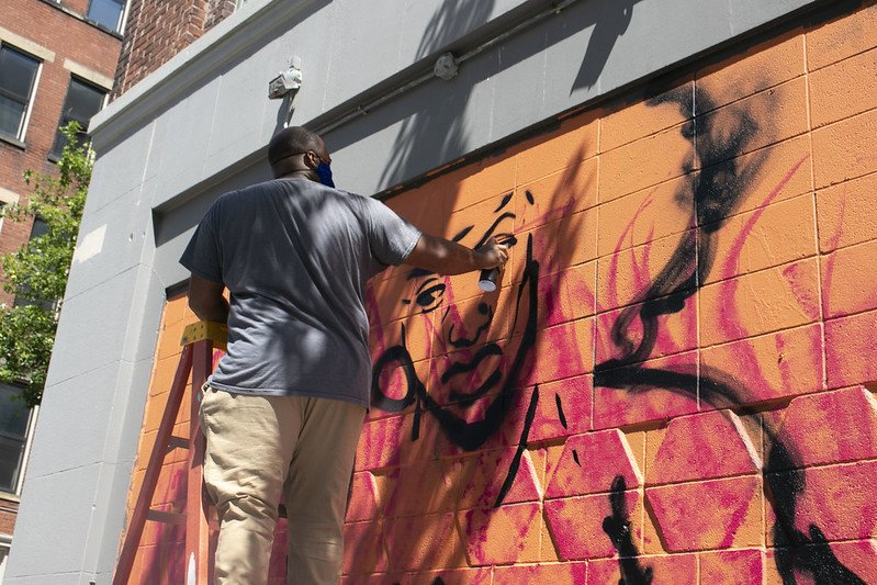 David Michael Butler is painting a mural on the side of the Art Academy of Cincinnati.
