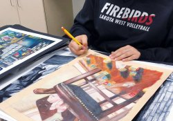 An image of a student going through a portfolio of artwork.