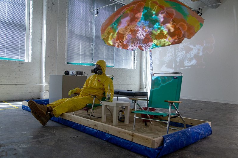 A photograph of Michael Lee sitting on his installation.