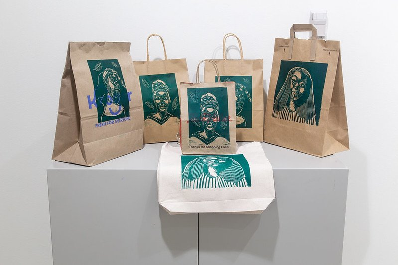 Relief print portrait images printed on used paper bags.