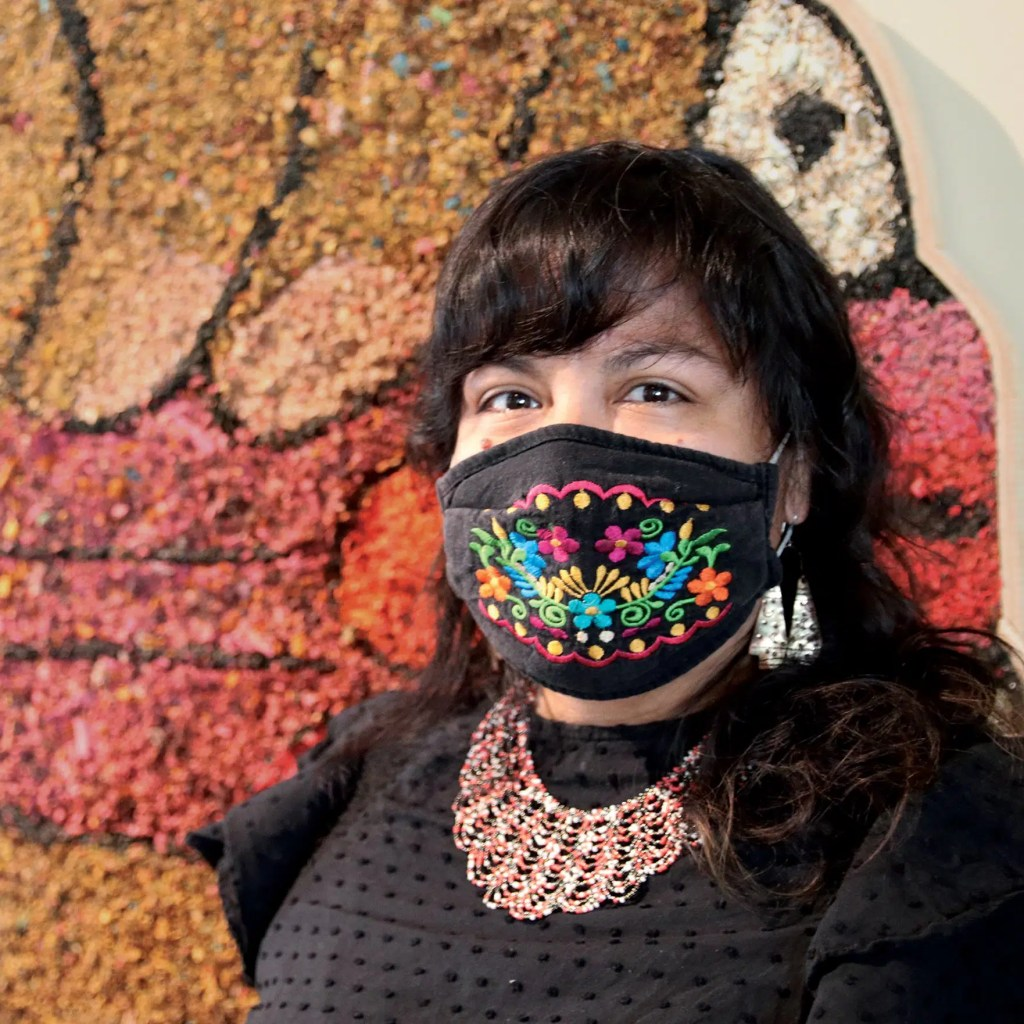 A photograph of Rebecca Nava in front of her work.