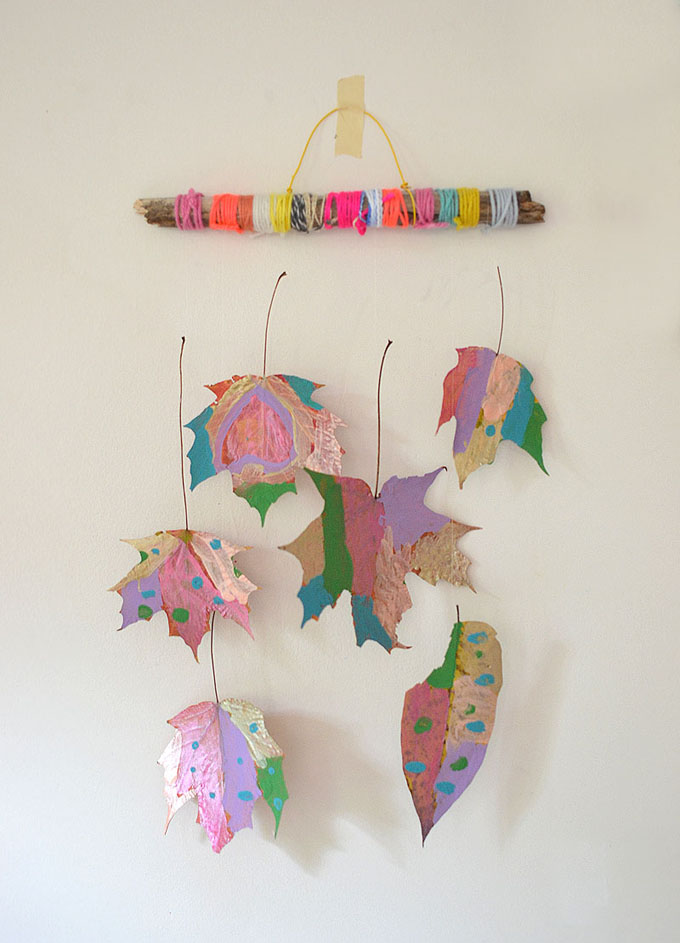 Kids paint leaves and hang them from a twig to make a whimsical and gorgeous mobile.