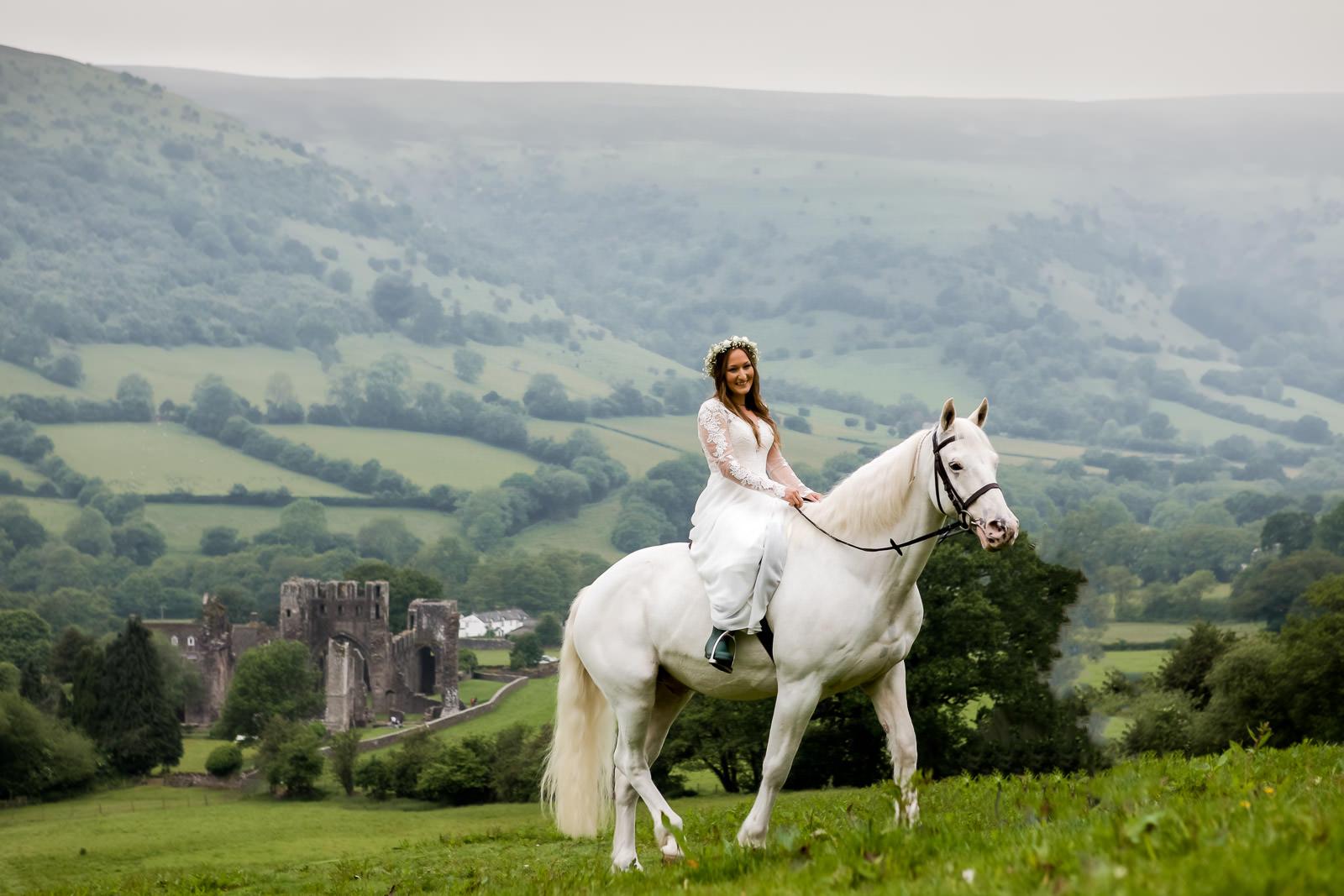 Boho farm wedding Wales - Bride arrives on white horse
