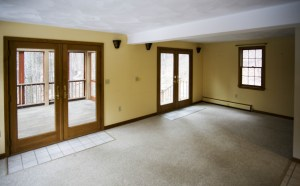 French doors open from the living room to the screened porch, deck, and garden waterfall
