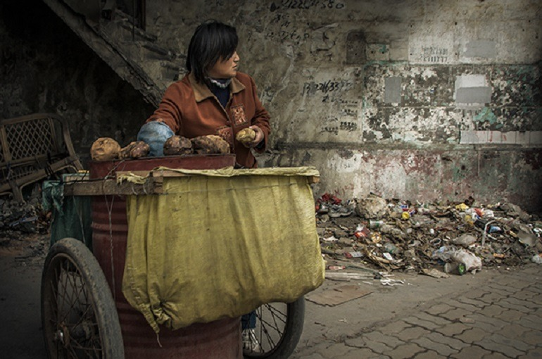 Image- Ron Gessel street photograph shows a street trader on the The Street 'The Streets of Shanghai. Besides is trash