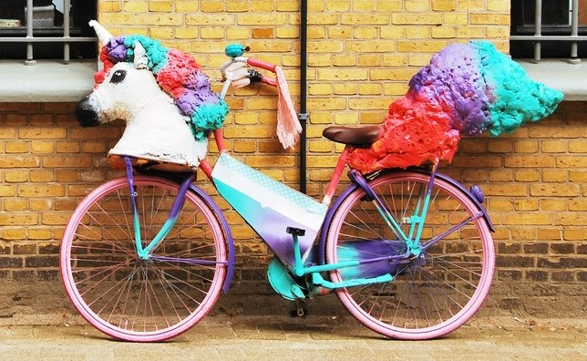 A unicorn sculpture mounted on a bicycle with pink, purple and blue paint.