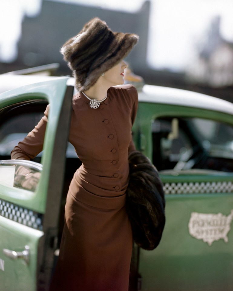 Model wearing a tight-fitting brown rayon dress with draped torso, a Vogue pattern, together with mink fur hat and stole from Gunther's.