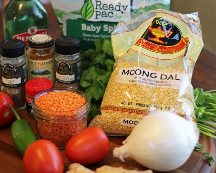 The ingredients for spiced lentils on a wood table.
