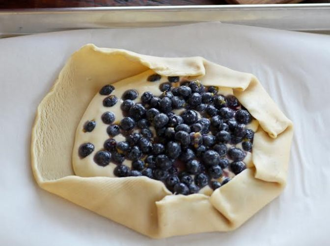 Folding the Pie Crust up over the Blueberry Cheesecake Filling | www.artfuldishes.com