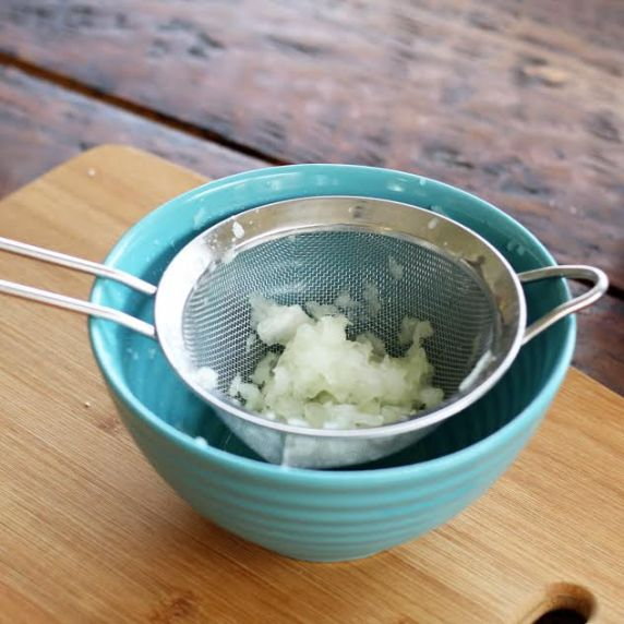 Straining grated onion over a blue bowl.