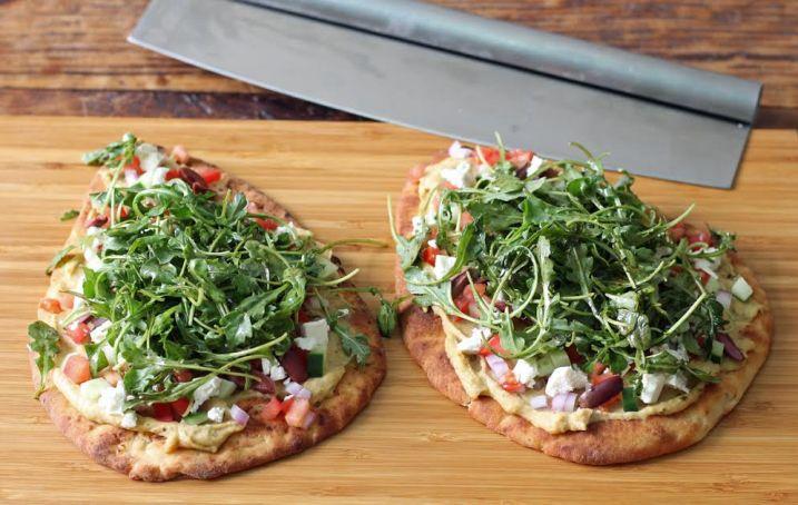 Adding the Arugula to the Greek Salad Naan Pizzas   www.artfuldishes.com