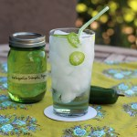 A glass of homemade jalapeno soda and a jar of jalapeno simple syrup on a green tablecloth.