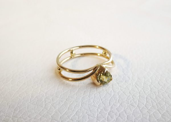 yellow gold ring made of two round wires separated by tiny balls. the main stone is a trillion cut chrysoberyl.