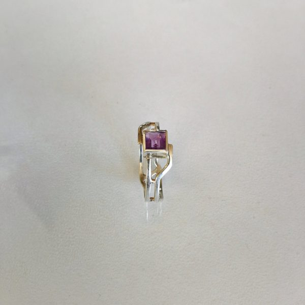 Sterling silver ring with a sci-fi design and a square amethyst. the two bands are separated by golden balls