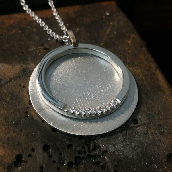 brushed silver coin attached to a polished silver ring set with laboratory grown diamonds