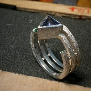 three silver rings with an iced finish. Central stone is a triangle iolite, two stones set in the ring are green topazes.