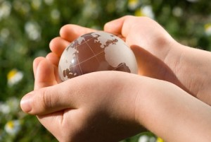 We've got the world in our hands - image of a child's hands carrying a glass globe.