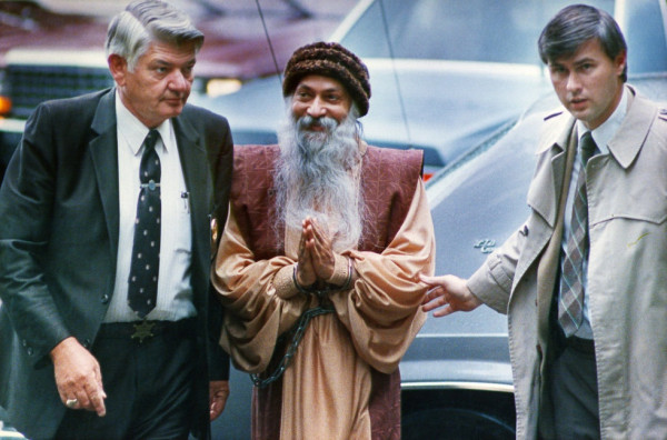 Rajneesh being escorted by federal agents.
