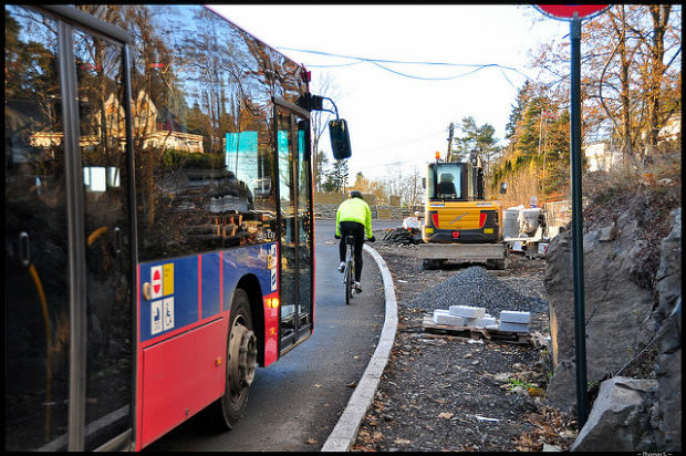 carbon neutral: Bus shares the road with a biker