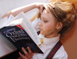 A girl holding a dictionary, trying to figure out what certain words mean.