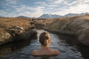 A woman in a hot spring enjoying nature.