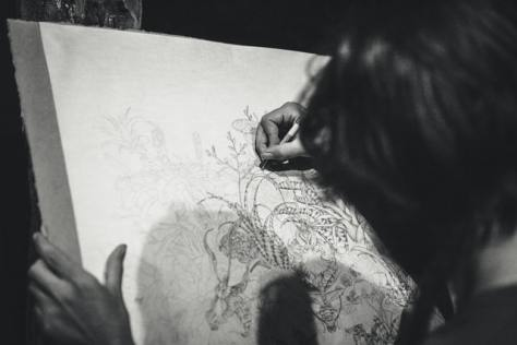 An artist drawing on canvas