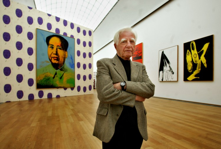 Erich Marx. A suit-jacketed man with grey hair stands in a museum gallery hung with Warhols.