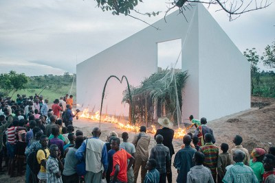 People gather outside a large white structure to watch it burn