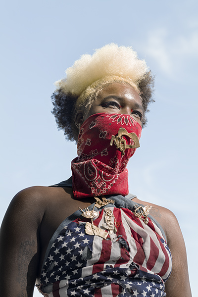 photo of a black woman wearing an American flag halter top and red bandana covering her face
