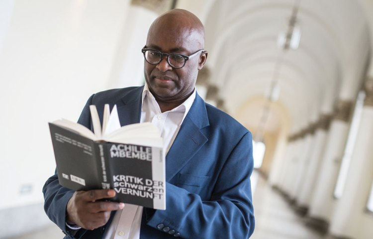 Achille Mbembe flipping through his award-winning book Critique of Black Reason (2015).