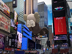 A gray digital figure appearing to float over Times Square covers its face with its hands, putting an X over each eye