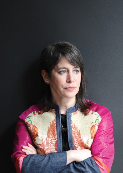 A portrait of Sara Reisman who is wearing a patterned jacket with magnet sleeves.