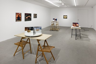 Installation view showing three rotating sculptures propped up on chairs and saw horses. The one in the foreground shows a photo of a potato. The rest are hard to make out, as are the four photos on the wall—except the large photo of a limp hot dog.
