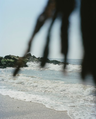 View of a beach obscured by locks covering the camera lens.