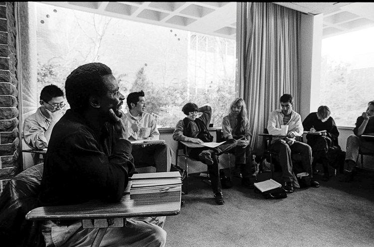 Archival photo of Charles Gaines, left, teaching at CalArts in 1992 with seated students in a circle.