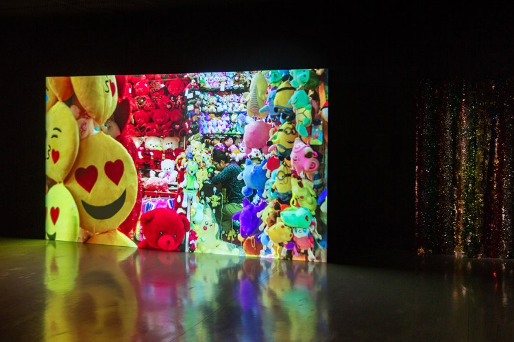 room with a large video screen showing a store filled with colorful stuffed toys