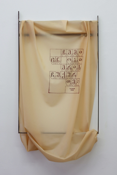 A beige latex sheet draped over a dark empty steel frame is painted with letters from the Georgian alphabet.