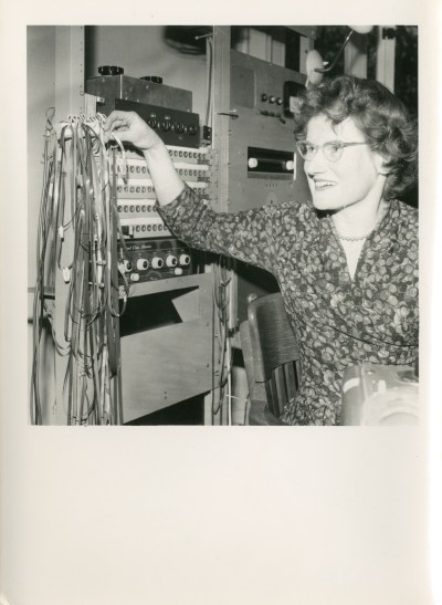 A grayscale photo of a white woman standing in front of vitage audio equipment.