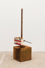 A stack of four books is gripped in a vice atop a cubic plinth of rusted steel