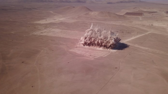 Still of Melanie Smith's 2018 video 'Maria Elena' showing a bombing in a desert.