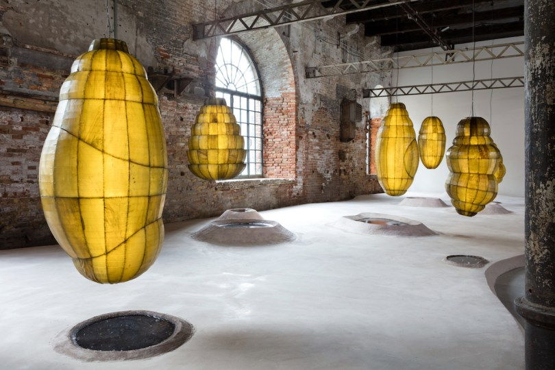 Floating semi-opaque sacs in an unfinished exhibition space with a concrete floor.
