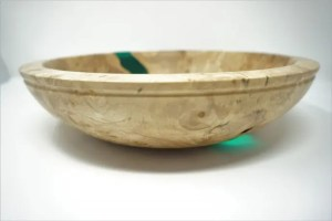 Side view of maple burl bowl with epoxy inlay and light refracting through the epoxy