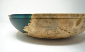 Detailed side view of a wood turned bowl made from silver maple and teal translucent epoxy resin.