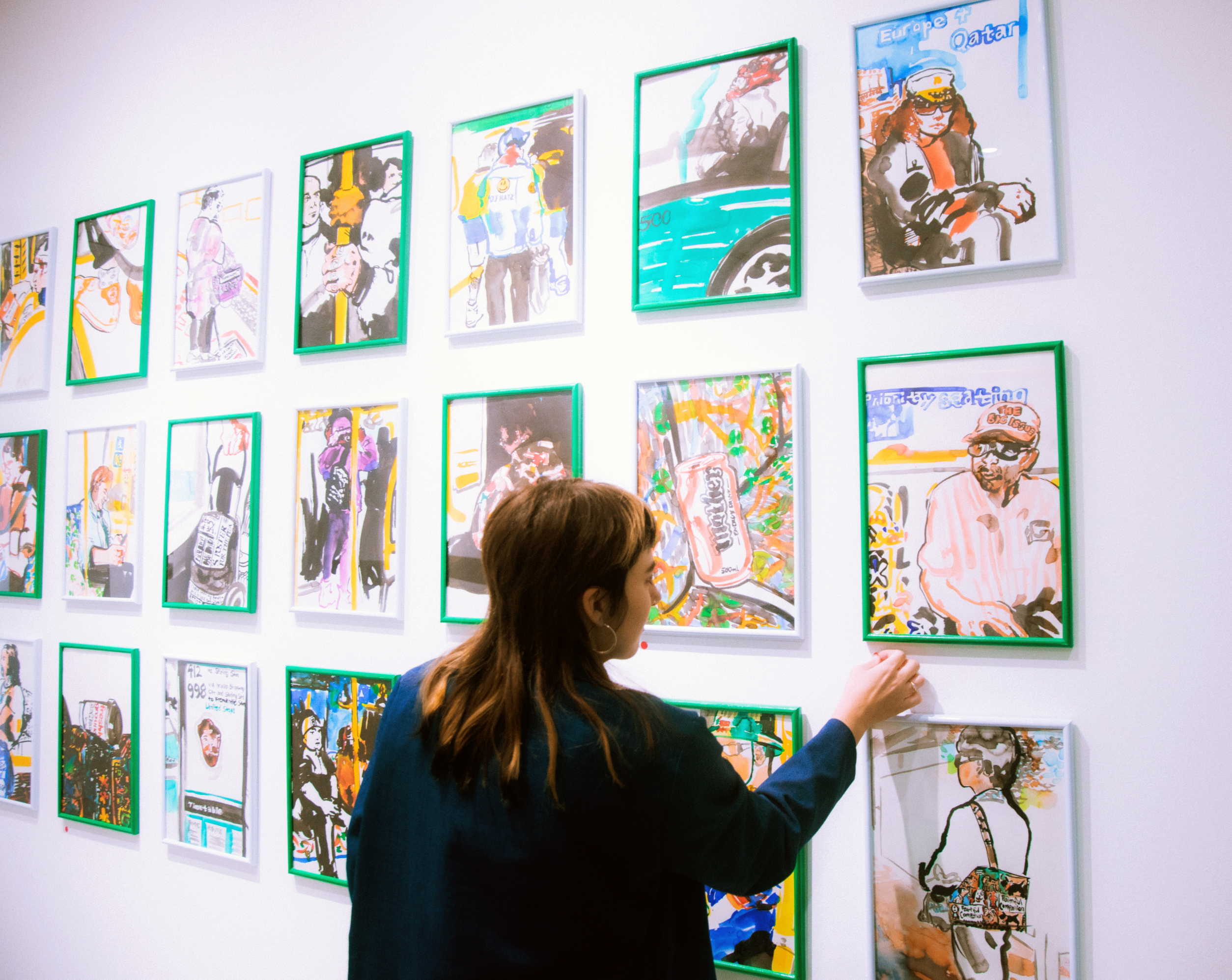 A yoougn female adjusting artworks on the wall of a gallery
