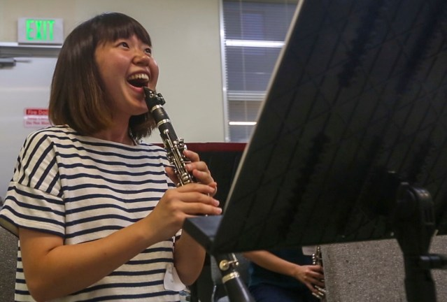 A student laughs during a clarinet lesson.