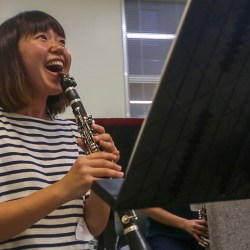 A student laughs during a clarinet lesson. Photo by Daniel Jean-Paul