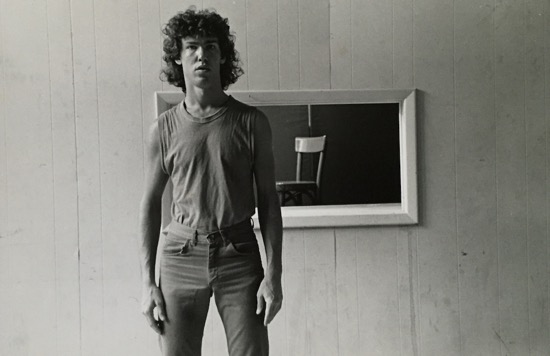 John Bernd in the 1980s, photographed by Dona Ann McAdams in front of am image of his red chair